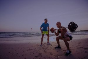 man exercising with a personal trainer in Dubai