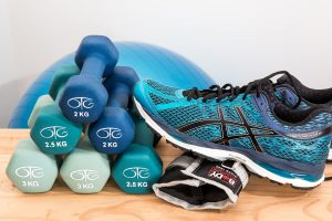 A blue trainer next to blue dumbbells.