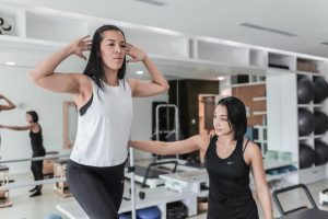 A girl works out with a trainer in a gym