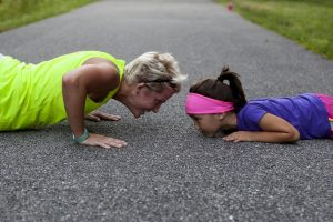 A woman and a child doing push-ups.