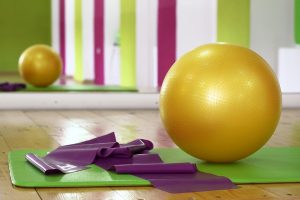 A yellow pilates ball on a green yoga mat.