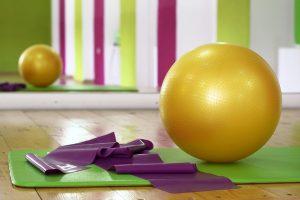 A yellow pilates ball on a green yoga mat.