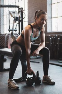 Woman in the gym holding kettlebell
