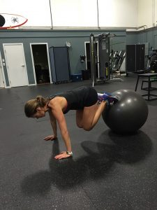 a lady doing a variation of a plank in her HIIT workout
