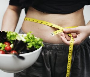 Woman with a salad and meter around belly