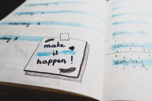 "Notebook with words ""make it happen"" written on it"