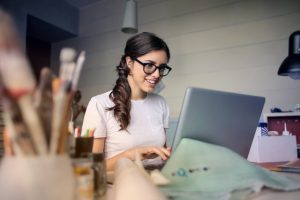 Woman sitting in front of computer, smiling