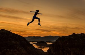 Woman jumping from one hill to another during sunset