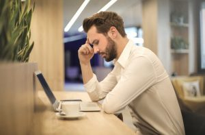Man sitting in front of computer, frowning