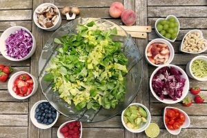 Healthy foods: big green salad with many small side salads and some fruit