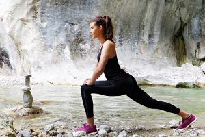 Girl in workout clothes stretching by a river