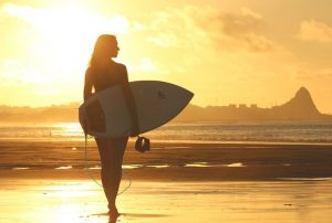 Girl holding a surfboard on the beach at sunset