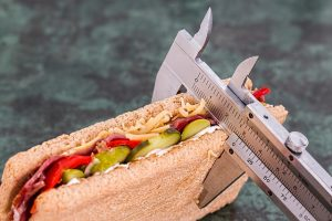 A sandwich measured by a tool symbolising monitoring calorie intake