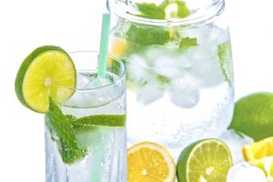 Pitch and a glass filled with ice water and lime and mint leaves