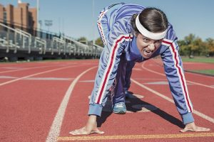 Girl in sweats on the running track prepared to do one of workouts for busy moms