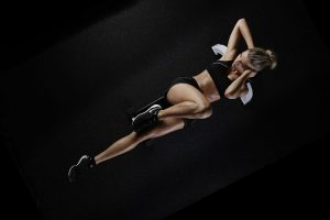 A girl doing crunches on a black mat in all bleck workout gear
