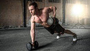 Man doing plank combined with lifting weiths.
