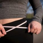 woman measuring waist width