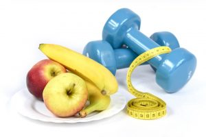 Weights, apples, and bananas on a white surface.