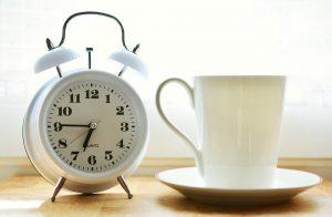 A white alarm clock next to a white coffee mug.