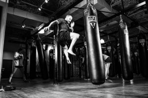 Man doing a high kick at a boxing bag in a black and white photo