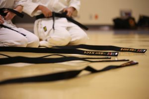 Black karate belts on the floor, some people in the back with kimonos
