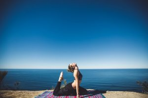 Girl in a yoga pose by the sea