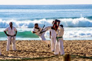 Karate masters high kicking on the beach