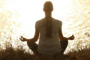 Woman in a yoga pose enjoying amazing benefits of Prenatal Yoga by a lake