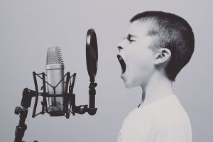 Kid yelling at a microphone in black and white about best exercise games for kids