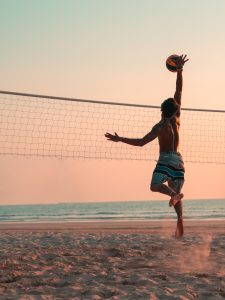 man staying fit while on vacation playing volleyball on sand