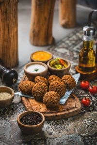 plate of falafel surrounded by spices and dips