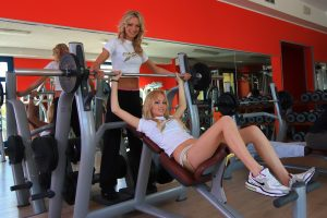 two women in gym talking as one of the benefits of group training