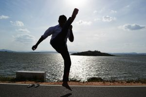 man doing karate kick as one of the benefits of karate for adults