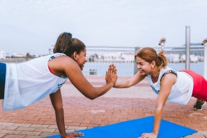 Discipline yourself to excercise daily by working out with a friend - two girls high-fiving while working out.
