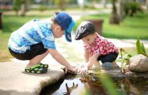 Two boys playing in a pond.