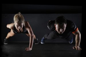 GIrl and guy doing push ups on one arm