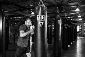 A man kicking a boxing bag.