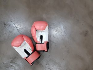 a pair of pink gloves on the floor showing facts about boxing
