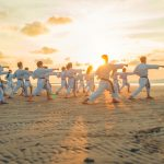 people in white robes training karate in sunset