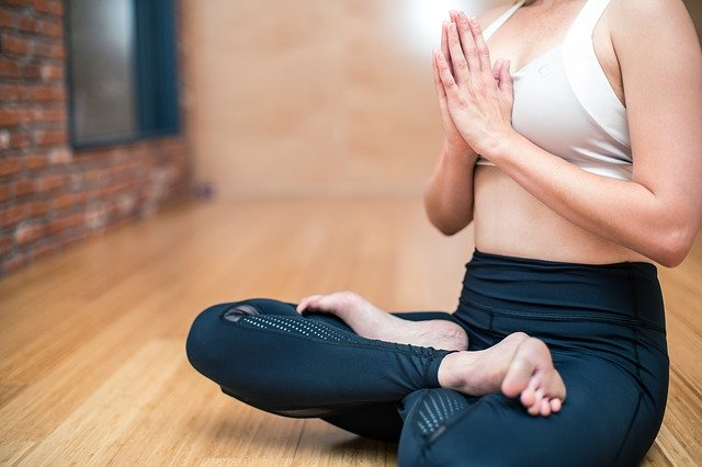 a woman practicing yoga, one of the hobbies that keep you fit and healthy