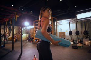 woman in gym clothes holding a blue mat