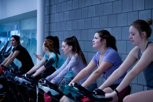 a row of women on exercise bikes