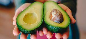 A person holding avocados.
