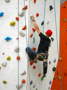 A man participating in indoor rock climbing for beginners.