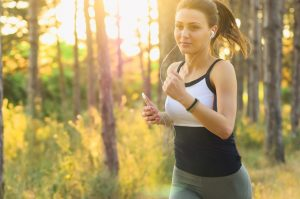 A woman jogging in a park - a good exercise to beat anxiety.