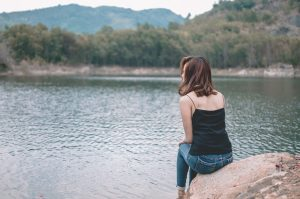 A girl sitting on a rock and looking at the lake.