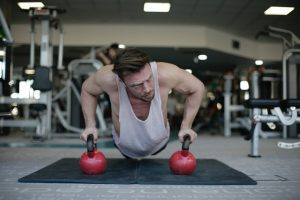 man doing push-up with dumbbells