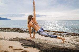 pilates vs. yoga - woman doing yoga on a beach