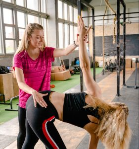 a PT helping a woman do a windmill